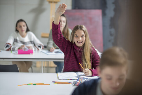 Happy teenage girl raising hand in class - ZEF15674