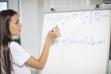 Teenage girl writing formula on whiteboard - ZEF15680