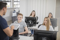 Teacher talking to students in computer class - ZEF15695
