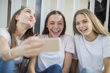 Happy teenage girls sharing cell phone in school - ZEF15725