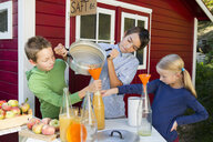 Teenage boy and siblings pouring fresh orange juice to sell at roadside - CUF24422