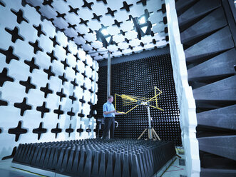 Engineer checking the bilog antenna set up for electromagnetic compatibility (EMC) radiated emissions in anechoic chamber with energy absorbers - CUF24440