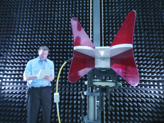 Engineer in anechoic chamber with horn antenna set up for electromagnetic compatibility (EMC) radiated emission testing - CUF24449