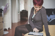 Young woman at home using digital tablet - CUF24497