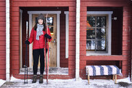 Portrait of young female skier on cabin porch, Posio, Lapland, Finland - CUF24599