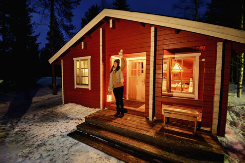 Young woman looking out from cabin porch at night, Posio, Lapland, Finland - CUF24602