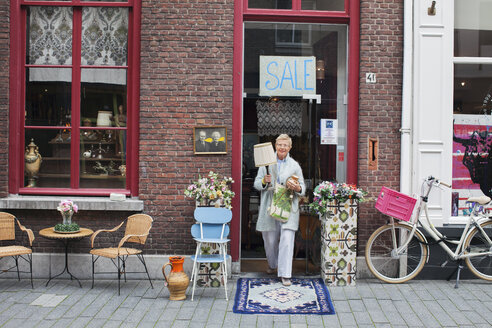 Mature female customer carrying lamp outside vintage shop - CUF24638