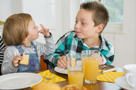 Cute female toddler licking fingers at kitchen table - CUF24686