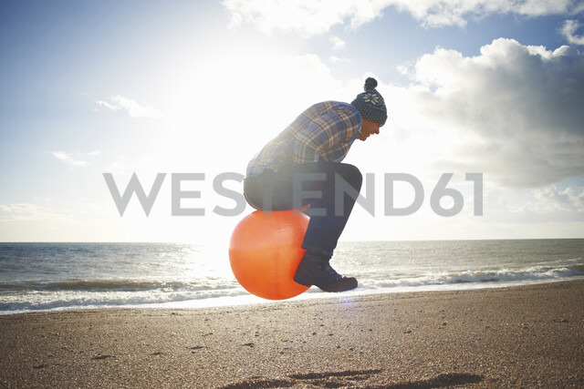 Mature man jumping mid air on inflatable hopper at beach - CUF24746 - Peter Muller/Westend61