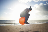 Mature man jumping mid air on inflatable hopper at beach - CUF24746