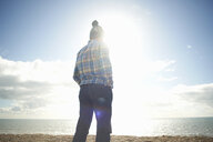 Mature man looking out to sea from beach - CUF24749