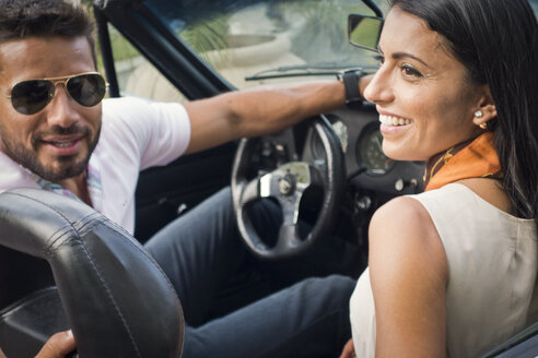 Mid adult couple in convertible car, rear view - CUF24752