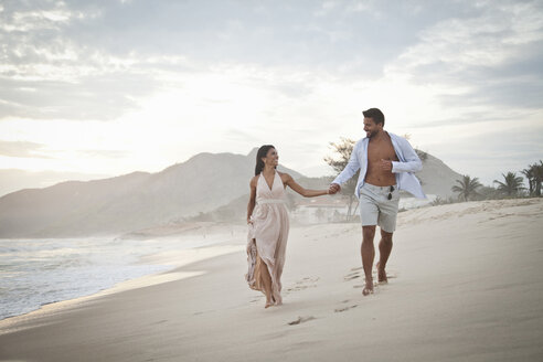 Mid adult couple walking along beach, hand in hand - CUF24767