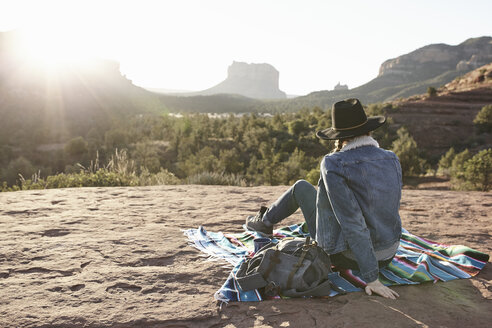 Woman sitting on blanket in desert, looking at view, rear view, Sedona, Arizona, USA - ISF09390