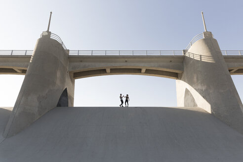 Couple holding hands under bridge, Van Nuys, California, USA - ISF09405
