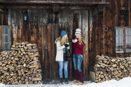 Two young female friends chatting outside wooden cabin - CUF25026