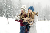 Two young female friends carrying logs in snowy mist - CUF25029