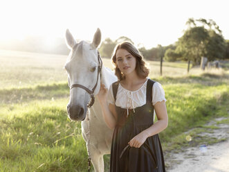 Portrait of teenage girl and her grey horse - CUF25035
