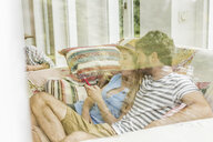 Window view of young couple on living room sofa reading smartphone texts - CUF25170