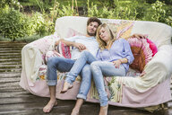 Couple relaxing on vintage sofa in garden - CUF25176