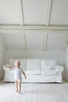 Portrait of baby girl toddling and pointing in living room - CUF25257