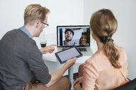 Colleagues sharing laptop video call with partners - CUF25323