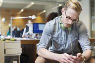 Young man choosing music from smartphone in office - CUF25344