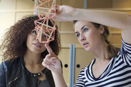 Two young female designers looking at handmade model in creative office - CUF25350