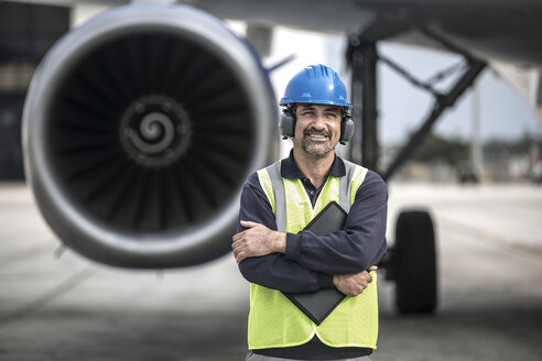Portrait of male worker in front of airplane at airport - CUF25467