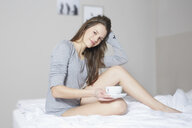 Portrait of young woman sitting on bed drinking coffee - CUF25530