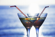 Close up of two cocktails in front of sunlit sea - CUF25590