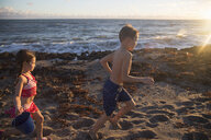 Boy and sister running on beach, Blowing Rocks Preserve, Jupiter Island, Florida, USA - ISF09429