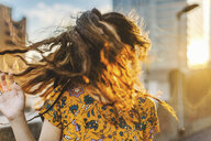 Front view of young woman shaking her long wavy hair in city sunlight - ISF09564