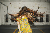 Front view of young woman shaking her long wavy hair in indoor carpark - ISF09567