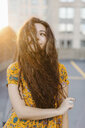 Portrait of young girl pulling long wavy hair across face in parking lot - ISF09573