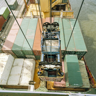 Shipping container being lowered by crane onto ship in port, high angle view - CUF25754
