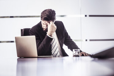 Stressed businessman with hand on forehead at office desk - CUF25814