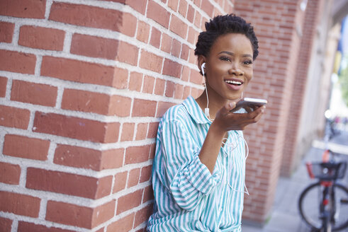 Portrait of smiling woman with earphones on the phone - ABIF00553