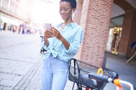 Portrait of smiling woman with earphones and cell phone in the city - ABIF00556