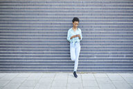 Woman standing in front of grey facade using cell phone - ABIF00571