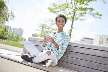 Portrait of smiling young woman with cell phone and earphones sitting on bench - ABIF00577