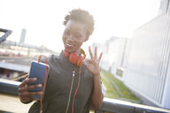 Portrait of young woman with    headphones taking selfie with smartphone - ABIF00586