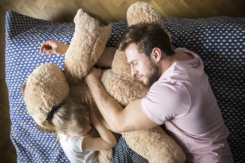 Father and daughter taking a nap, cuddling with teddy bear - AWF00008