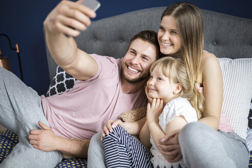 Happy family sitting on bed, taking smartphone selfies - AWF00026