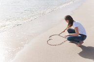 Woman drawing heart shape in sand on beach - CUF25938