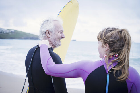 Father and daughter with surfboard on beach - CUF25965