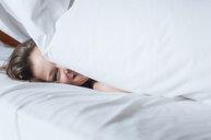 Happy woman under duvet in bed - CUF25998