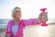 Senior woman exercising with weights by beach - CUF26037