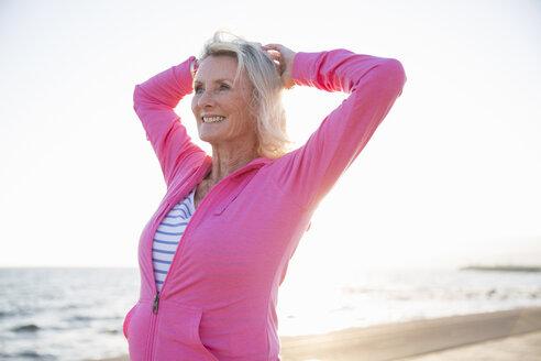 Senior woman stretching by beach - CUF26040