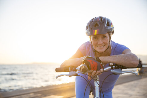 Senior woman on bicycle by beach - CUF26043